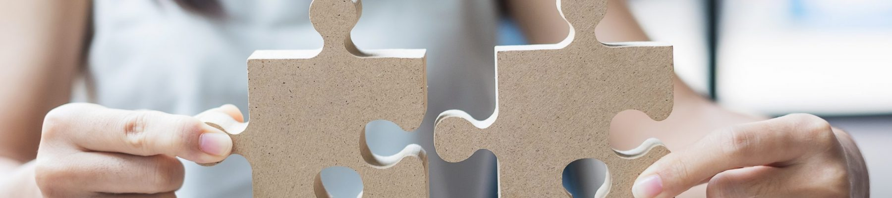 woman hands connecting couple puzzle over table, businesswoman holding wood jigsaw inside office. Business solutions, mission, target, success, goals and strategy concepts